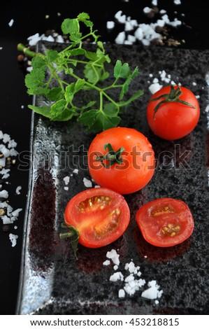 Fresh cherry tomato with sea salt on black tray - stock photo