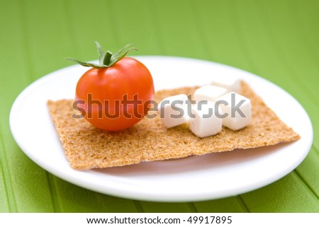 Fresh cherry tomatoes and greek cheese on plate - stock photo
