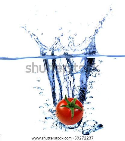 Fresh cherry tomatoes dropped into the water - stock photo