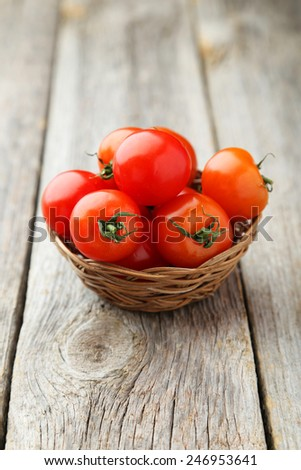 Fresh cherry tomatoes in basket on grey wooden background - stock photo