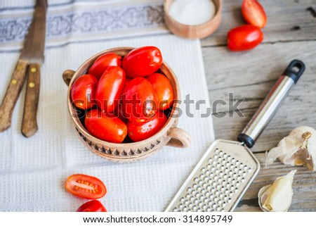 Fresh cherry tomatoes in pottery on a gray wooden table, rustic,selective focus