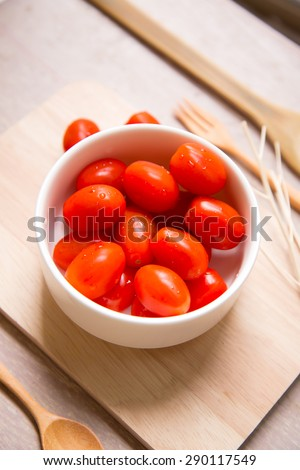 Fresh cherry tomatoes in white bowl decorated with wooden spoon and fork. - stock photo