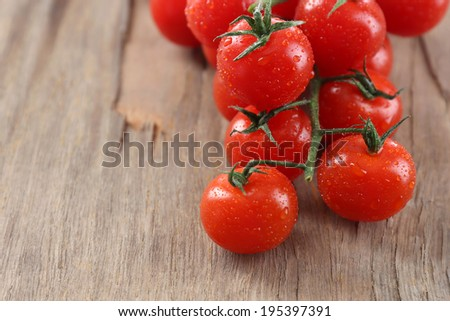 Fresh cherry tomatoes on old wooden table - stock photo