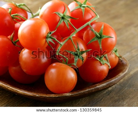 Fresh cherry tomatoes on wooden plate - stock photo
