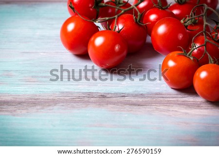 Fresh cherry tomatoes on wooden table - stock photo