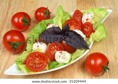 Fresh cherry tomatoes salad with seasoned mozzarella cheese and green lettuce