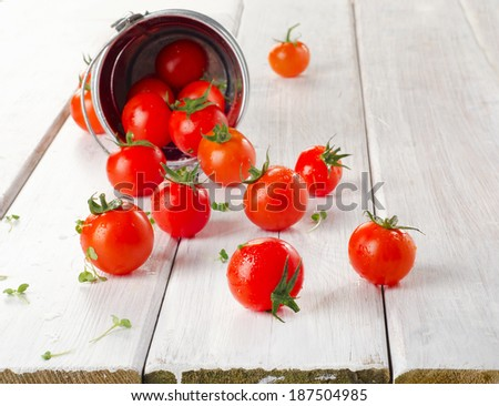 Fresh  cherry tomatoes with herbs on a wooden table. Selective focus - stock photo