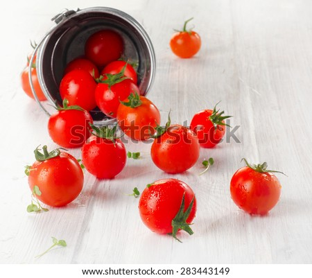 Fresh  cherry tomatoes with herbs on a wooden table. Selective focus