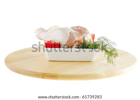 fresh chicken drumstick on wooden plate over white