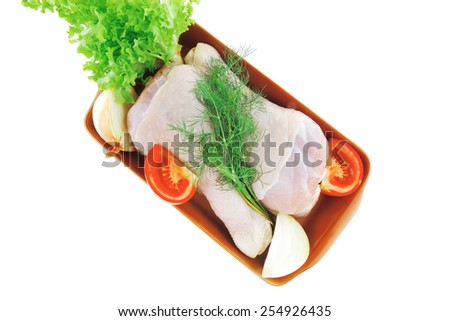 fresh chicken legs on bowl with green lettuce - stock photo