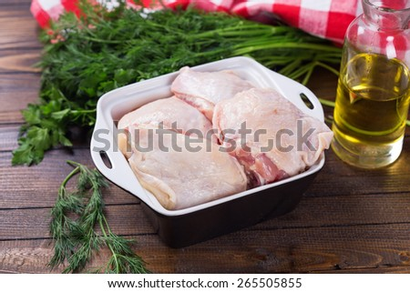 Fresh chicken meat in bowl  on painted wooden planks. Selective focus. Rustic style. - stock photo