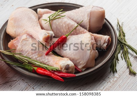 Fresh chicken meat on plate on white table with herbs. Selective focus. Rustic style. - stock photo