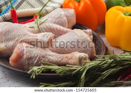Fresh chicken meat on plate  on white table with vegetables. Selective focus. Rustic style. - stock photo