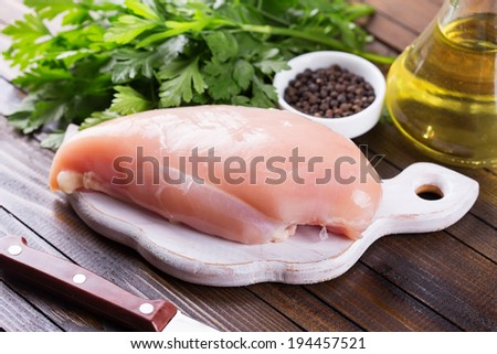 Fresh chicken meat on wooden board on table. Selective focus, horizontal. - stock photo