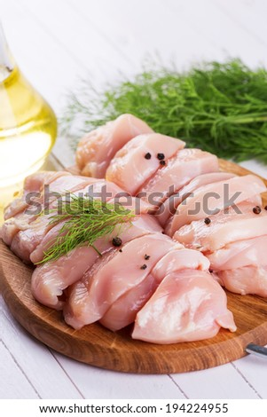 Fresh chicken meat on wooden board on table. Selective focus, vertical. - stock photo