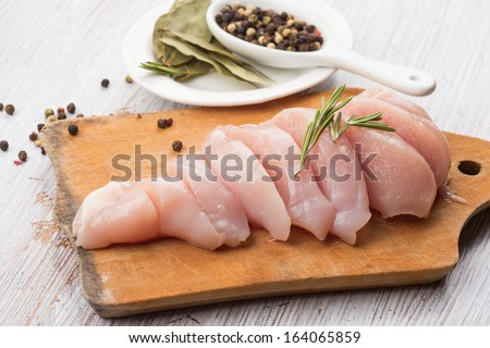 Fresh chicken meat on wooden board on white table. Selective focus. Rustic style. - stock photo