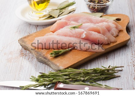 Fresh chicken meat on wooden board on white table with spices. Selective focus. Rustic style. - stock photo