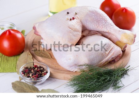 Fresh chicken meat on wooden board on white table with vegetables. Selective focus. Rustic style. - stock photo