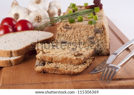 Fresh chicken pate with vegetables and herbs on a wooden chopping board - stock photo