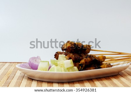 Fresh chicken satay on bamboo mat, one of famous Malaysian local dishes. - stock photo