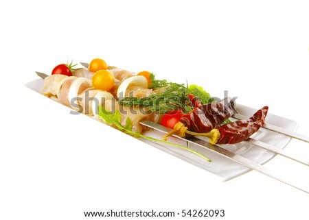 fresh chicken shish kebab on long white plate