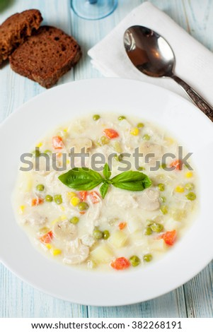 Fresh chicken soup with vegetables made of green pea, carrot, potato, selery, corn, onion, mushrooms  in bowl with basil, selective focus - stock photo