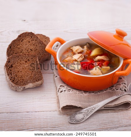 Fresh chicken soup with vegetables on white wooden table. Cutlery on a linen tablecloth. rustic style - stock photo