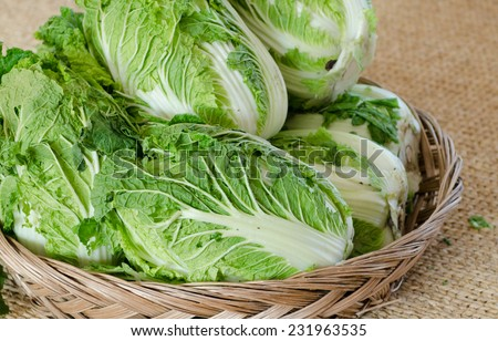 Fresh Chinese cabbage in the basket on sack background - stock photo