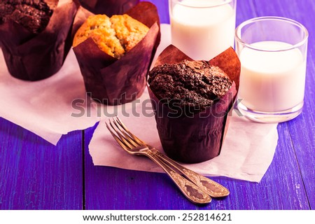 Fresh chocolate and vanilla muffins with milk on blue wooden background - stock photo