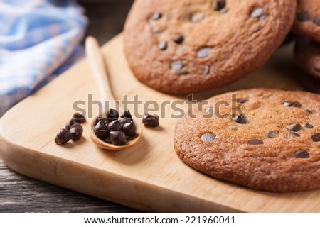 Fresh chocolate chip cookies setting on wood table - stock photo