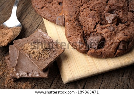 fresh chocolate cookies with chocolate chips on wooden desk - stock photo