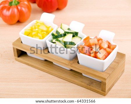 Fresh chopped paprika and zucchini in small porcelain bowls on wooden table