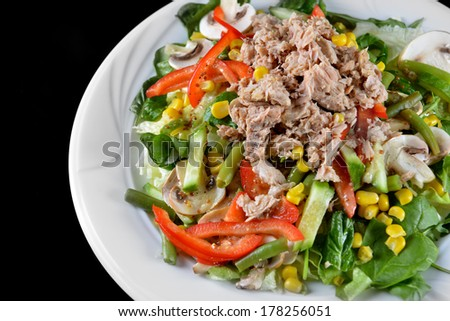 fresh chopped tuna salad with spinach on  black background - stock photo