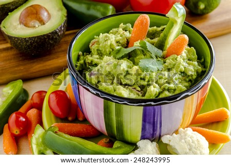 Fresh chunky guacamole in colorful bowl sitting on bright green plate garnished with raw carrots and green peppers and cilantro surrounded by raw vegetables