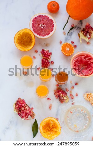 Fresh Citrus fruits and orange juice onto an marble background, top view. Organic,health y beverage.Vitamin drink. Citrus fruit background. Mediterranean diet.  - stock photo