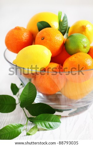 Fresh citrus fruits in the vase on a wooden table