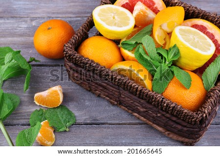 Fresh citrus fruits with green leaves in wicker basket on wooden background - stock photo