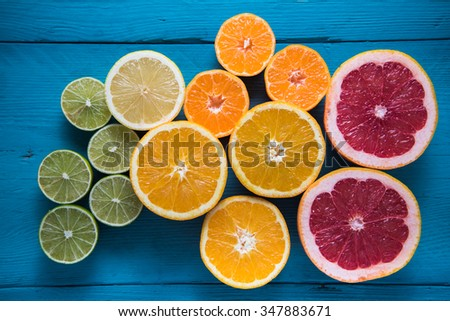 fresh citrus half cut fruits overhead on wooden table