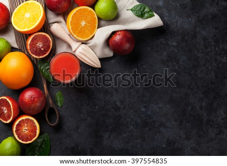 Fresh citruses and juice on dark stone background. Oranges and limes. Top view with copy space - stock photo