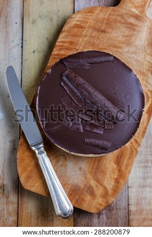 Fresh classic homemade Cheesecake with dark chocolate topping on wooden board and vintage table knife aside - stock photo