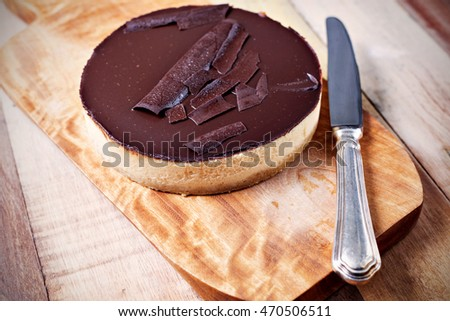 Fresh classic homemade Cheesecake with dark chocolate topping on wooden board and vintage table knife aside