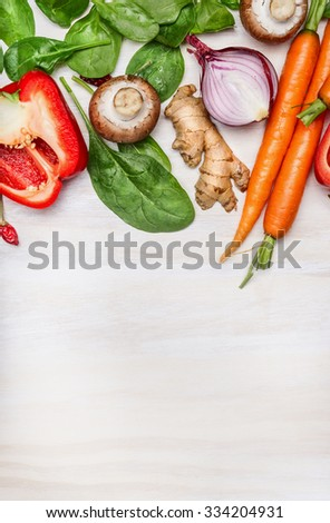Fresh clean garden vegetables for tasty cooking on white wooden background, top view. Place for text. Vegan and Healthy food concept.