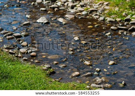 Fresh clear water fast flowing rocky mountain creek with vivid green grass on the bank - stock photo