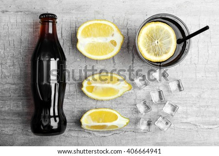 Fresh cocktail preparation:soda bottle,ice, lemons and glass - stock photo