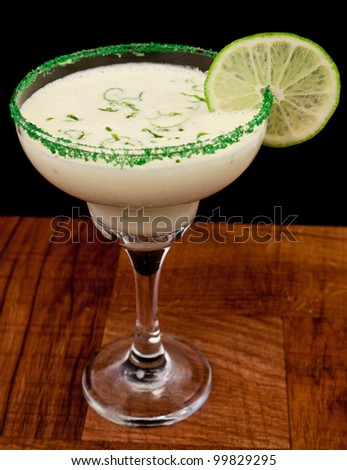 fresh cocktail served on a bar top garnished with green sugar and a lime wheel isolated on a black background - stock photo