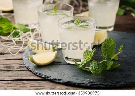 Fresh cocktail with lemon, ice and mint on the vintage table, selective focus - stock photo