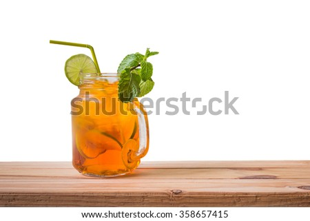 Fresh cocktail with lemon tea on wooden table over white background - stock photo