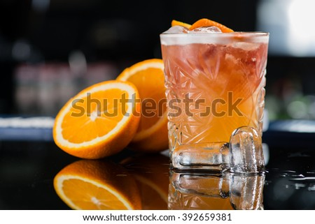 Fresh cocktail with orange and ice. Alcoholic, non-alcoholic drink-beverage at the bar counter in the night club. - stock photo