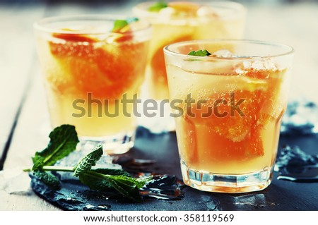 Fresh cocktail with orange, mint and ice, selective focus and toned image