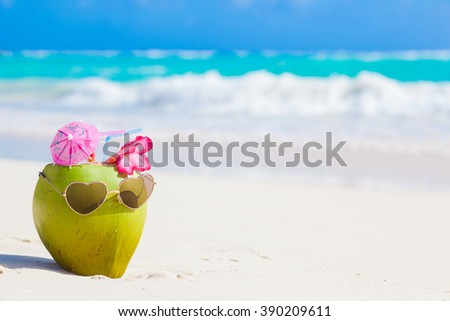 fresh coconut cocktail on tropical beach with flower - stock photo